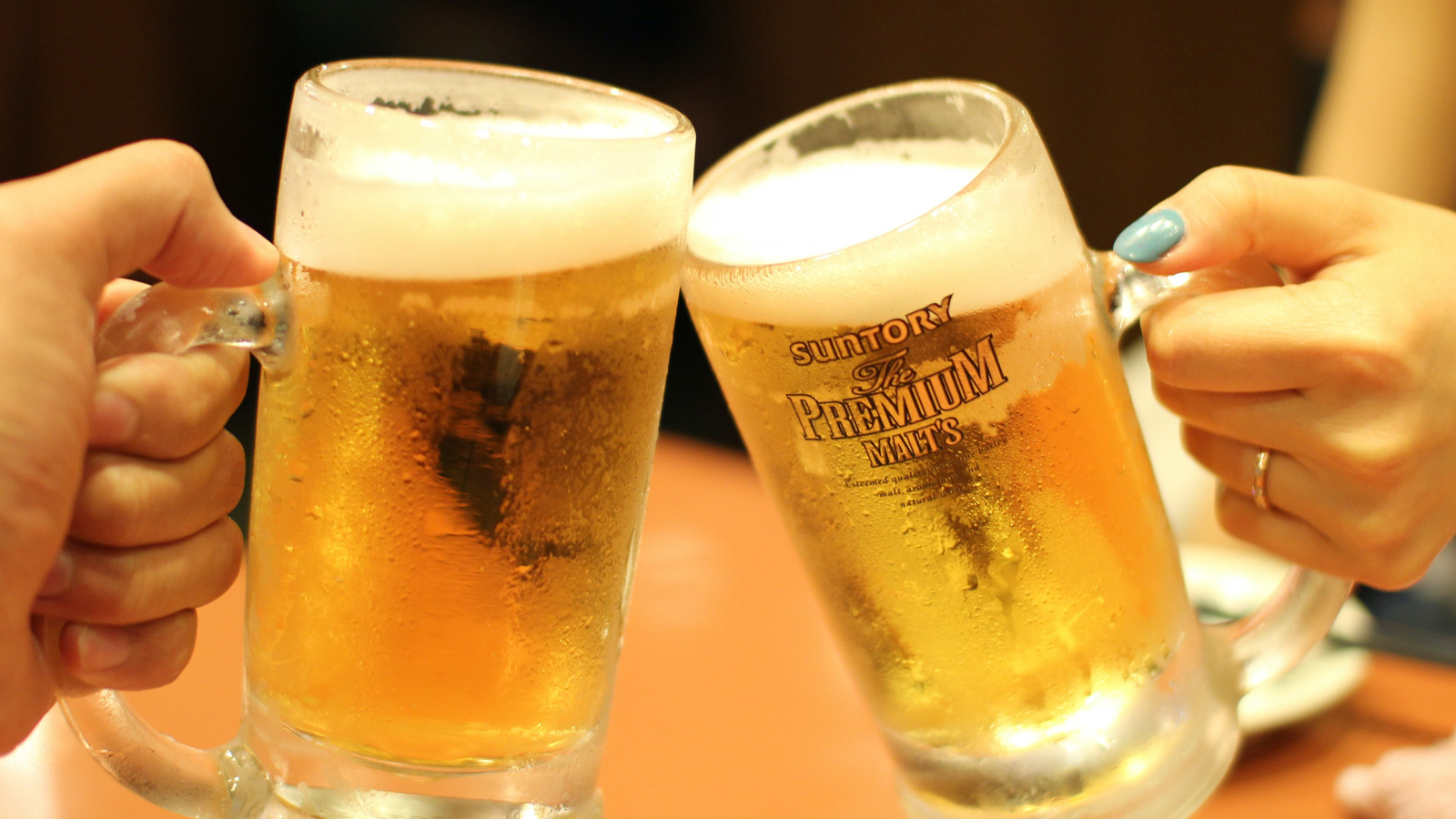"""Two glasses of beer touching in a """"cheers"""" gesture"""