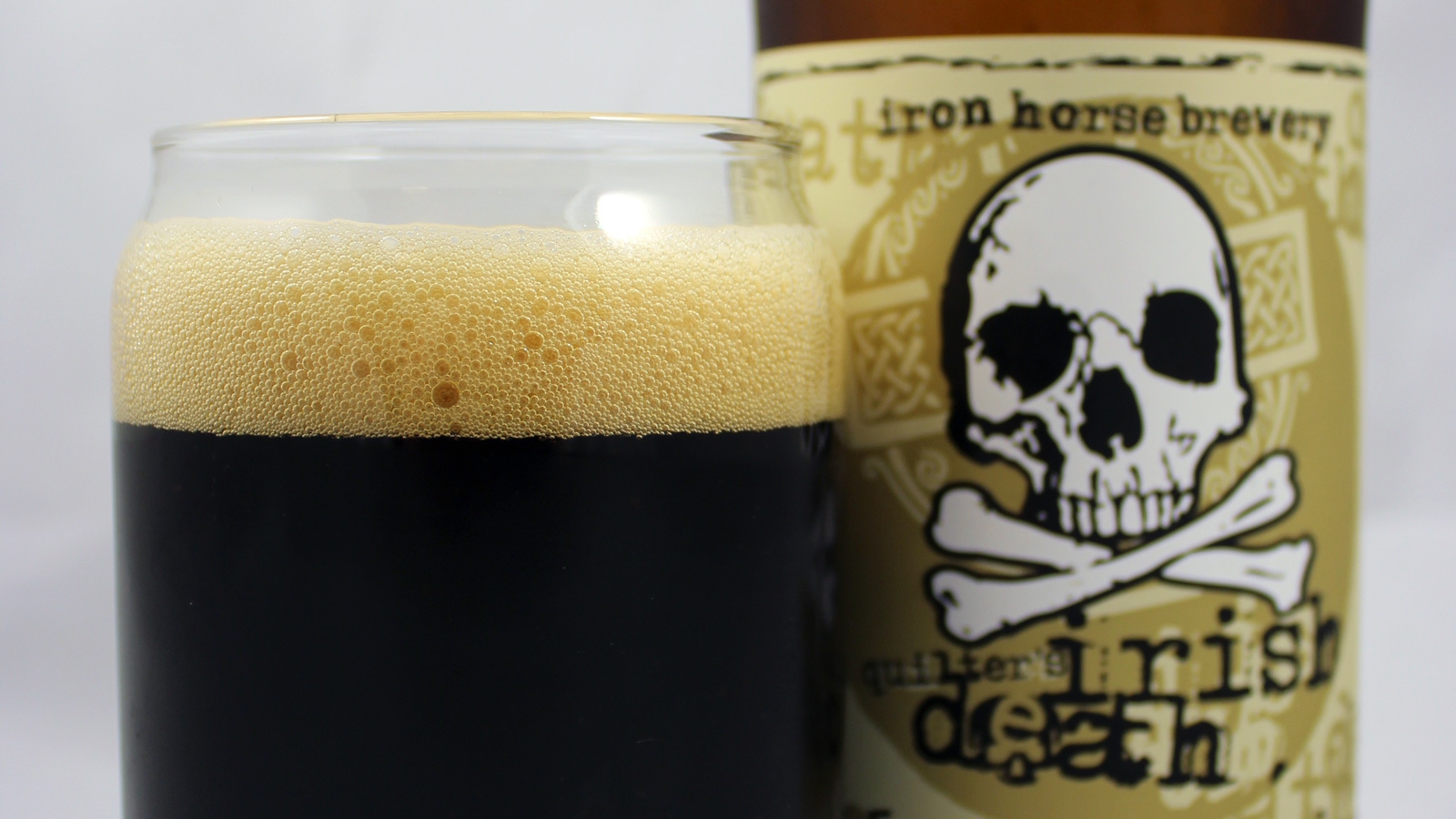 A glass of Irish Death beer next to its bottle