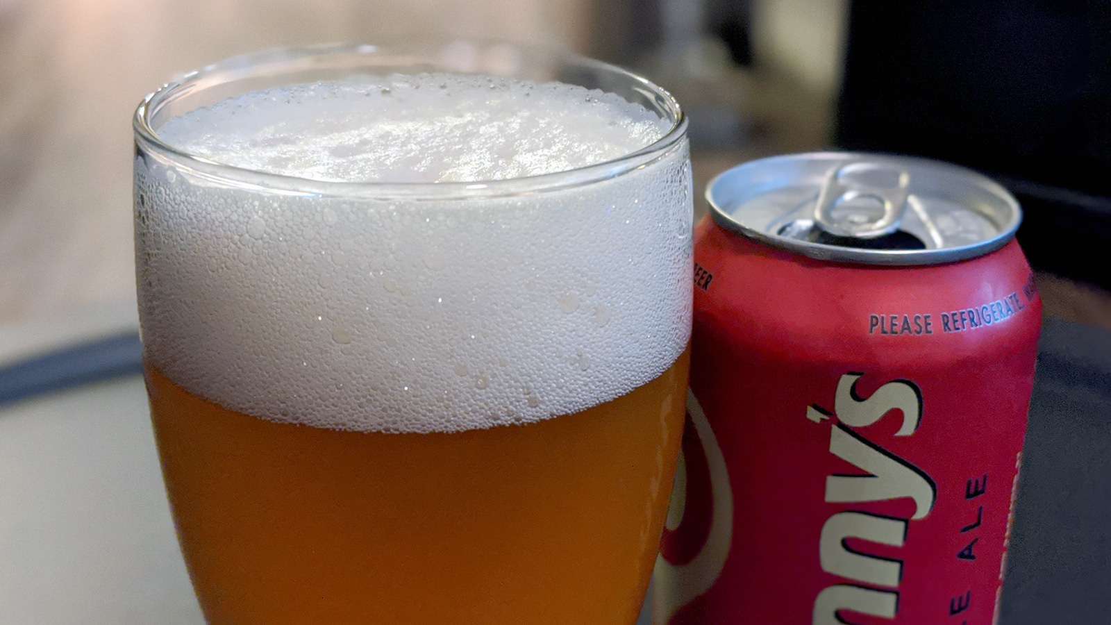 Close-up on the foam on top of a class of beer with its can to the side