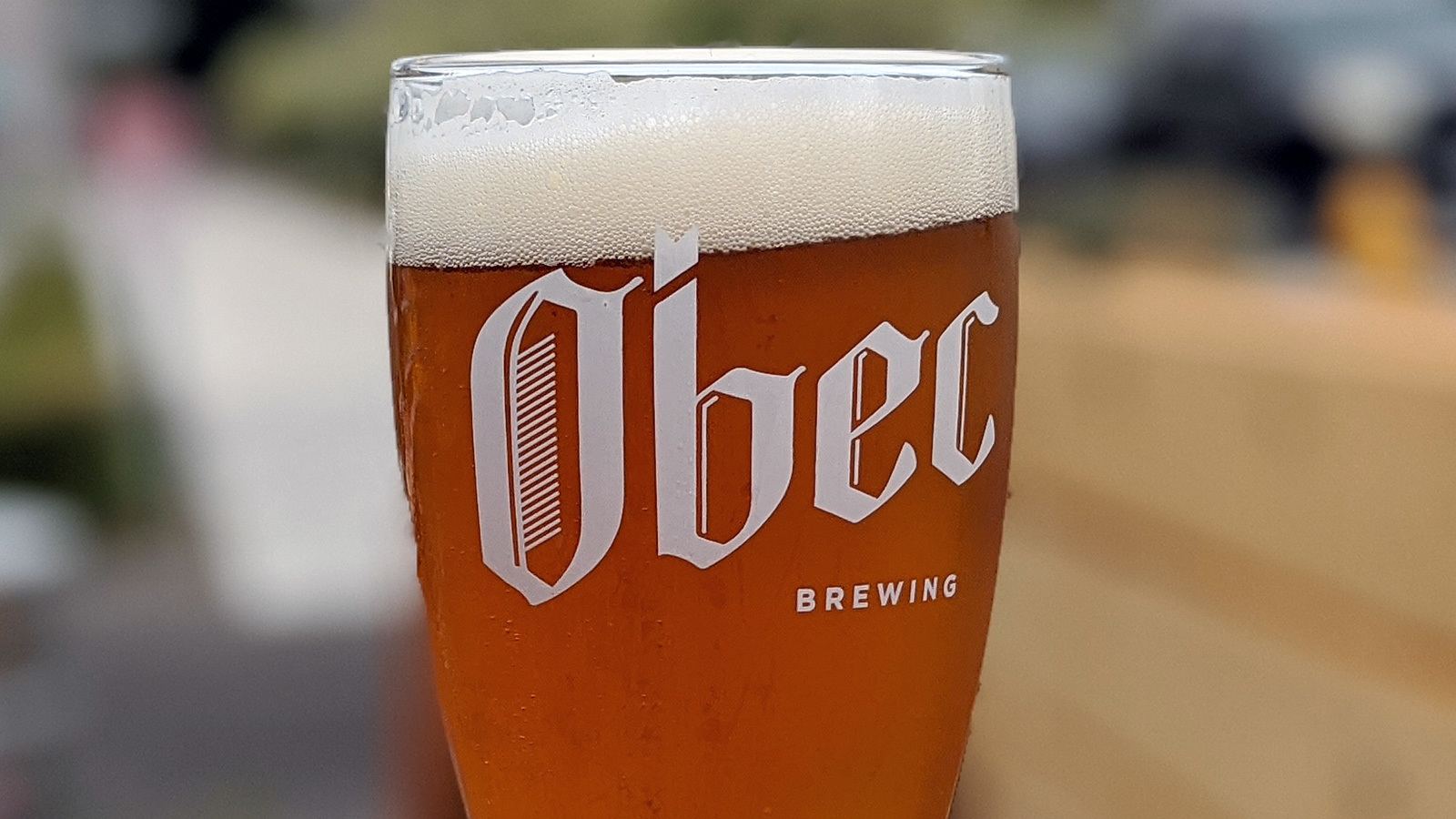 A glass of beer prominently displaying the Obec Brewing logo